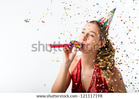 Woman celebrating birthday and hooting with horn at a shower of confetti - stock photo
