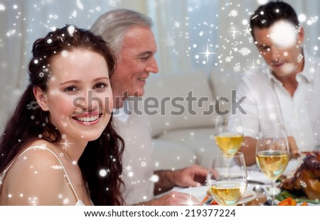 Woman celebrating Christmas dinner with her family against snow falling - stock photo