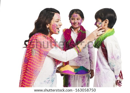 Woman celebrating Holi festival with her children - stock photo