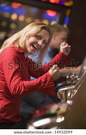 Woman celebrating win at slot machine in casino - stock photo