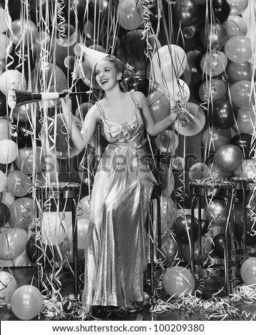 Woman celebrating with room full of balloons - stock photo