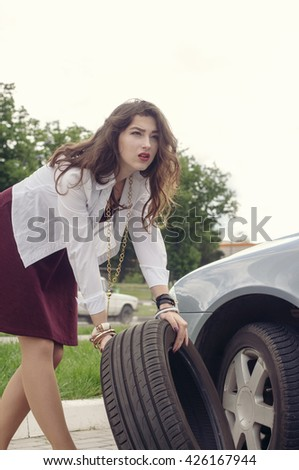 Woman changing car wheel. Concept: a road accident or replacement of rubber.