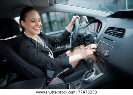 woman changing radio station while driving car - stock photo