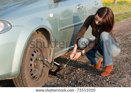 woman changing the broken Tire - stock photo
