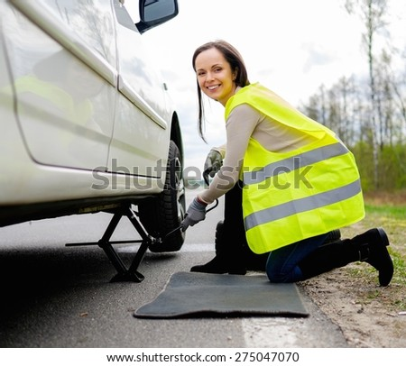 Woman changing wheel on a roadside  - stock photo