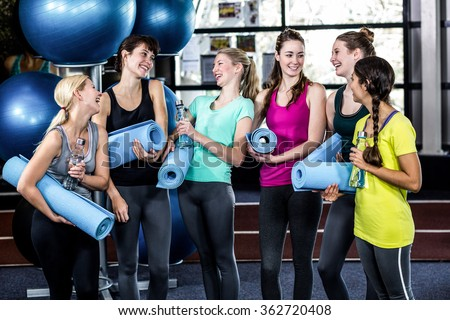 Woman chatting before yoga class in the gym - stock photo
