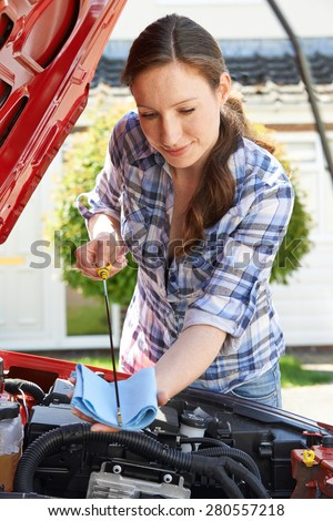 Woman Checking Car Engine Oil Level Under Hood With Dipstick - stock photo