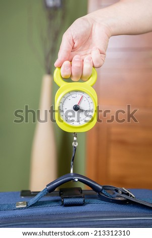 Woman checking hand luggage weight using a steelyard balance by low cost airlines restrictions - stock photo