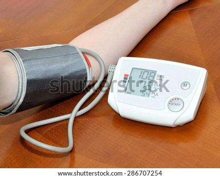Woman checking her blood pressure and pulse with digital instrument