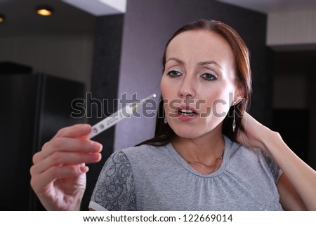 woman checking her body temperature - stock photo