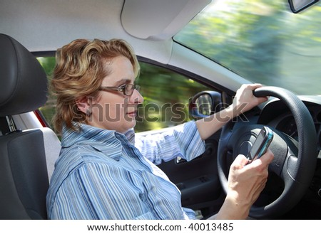 Woman checking her mobile phone while she drives her car. - stock photo