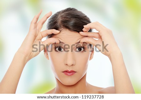 Woman checking her wrinkles on her forehead - stock photo