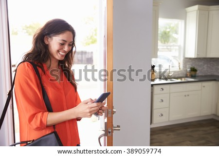 Woman Checking Mobile Phone As She Opens Door Of Apartment - stock photo