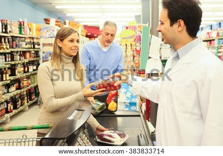 Woman checking-out at the supermarket - stock photo