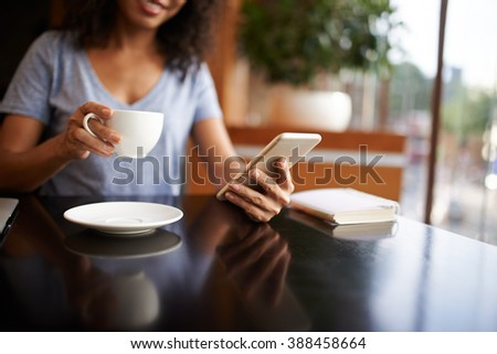 Woman checking social media on her smartphone, selective focus - stock photo