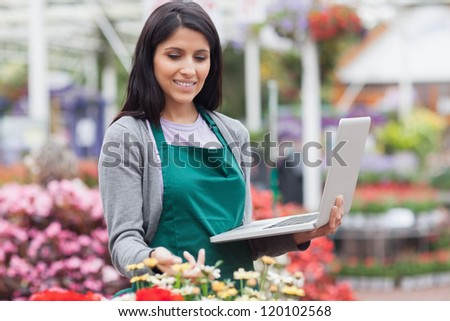 Woman checking stocks with a laptop in garden center - stock photo