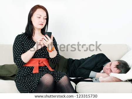 Woman checking telephone of her sleeping man - stock photo