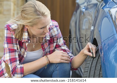 Woman Checking Tread Depth On Car tire - stock photo