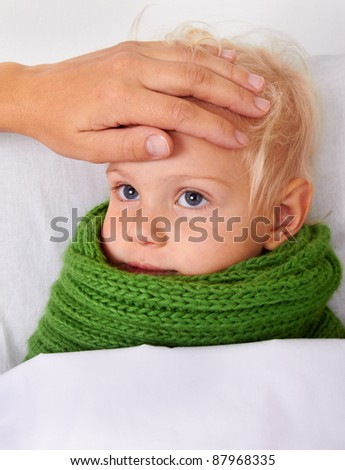 Woman checks the temperature of a sick baby - stock photo