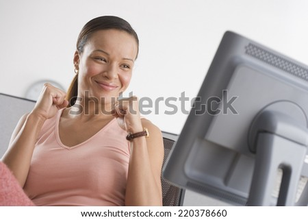 Woman cheering while looking at computer - stock photo