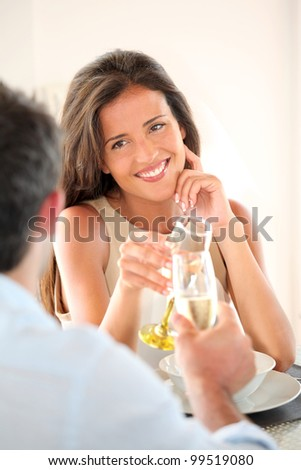 Woman cheering with glass of champaign in fancy restaurant
