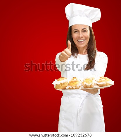 Woman chef holding baked food on red background - stock photo