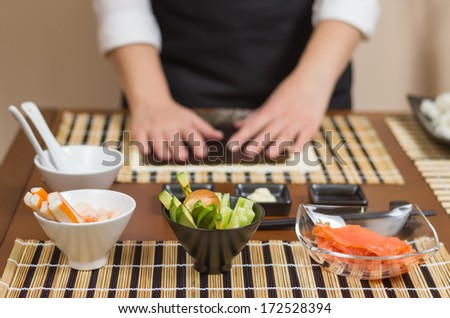 Woman chef ready to prepare japanese sushi rolls, with principal ingredients in the foreground