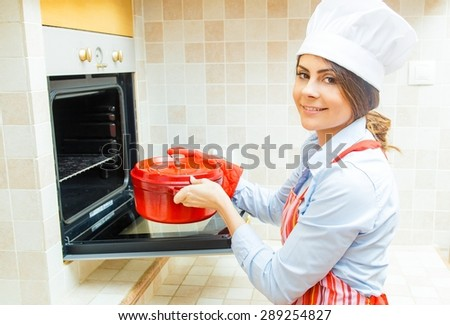Woman chef smiling and cooking in red pot in the kitchen.