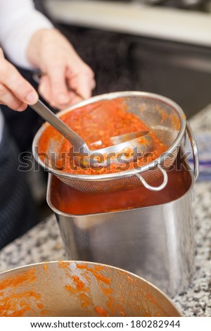 Woman chef whisking boiled tomato in a pot reducing them to a puree base for a soup or sauce using a handheld battery operated whisk - stock photo
