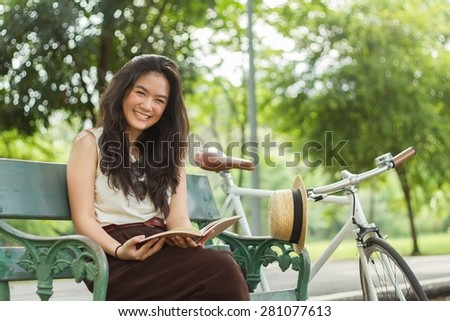 Woman chilling in the park with her book and her bicycle