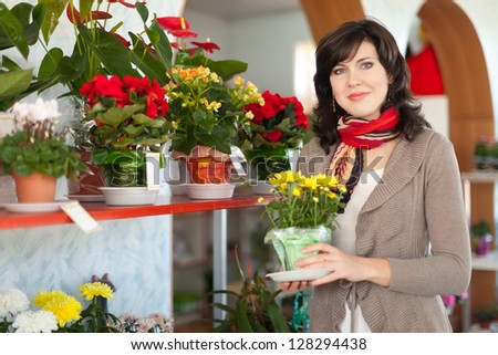 Woman chooses chrysanthemum in a flower shop