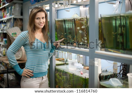 Woman chooses  fish in aquariums at pet-shop