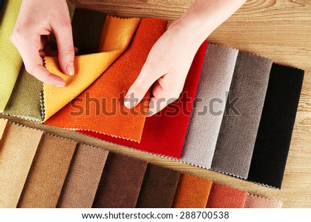 Woman chooses scraps of colored tissue on table close up - stock photo