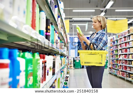 Woman chooses shampoo in cosmetics department in supermarket - stock photo