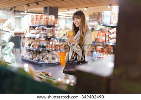 Woman choosing apples at supermarket and holding it - stock photo