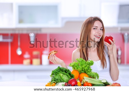 Woman choosing between croissant and an apple