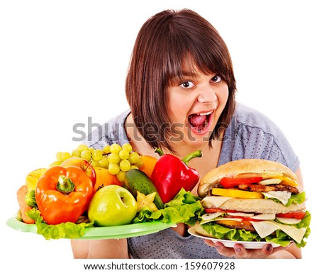 Woman choosing between fruit and hamburger. Isolated.