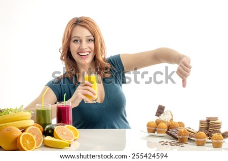 Woman choosing between fruits, smoothie and organic healthy food against sweets, sugar, lots of candies, unhealthy food. Treating your sweets addiction with fruits and vegetables - stock photo