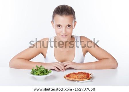 Woman choosing between salade and pizza - stock photo