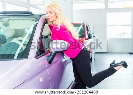 Woman choosing car for buying in dealership really desiring and kissing the auto - stock photo