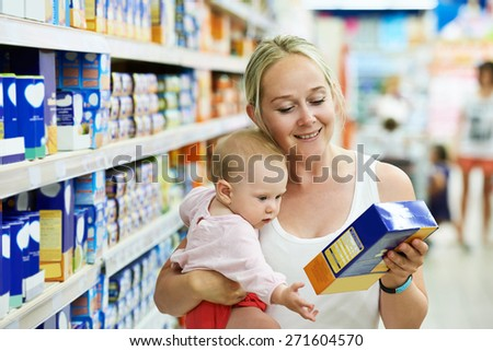 woman choosing children food with little baby child girl on hands during supermarket shopping - stock photo