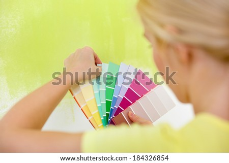 Woman choosing color for painting wall - stock photo