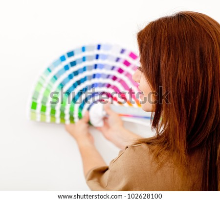 Woman choosing color to paint the wall from a guide - stock photo