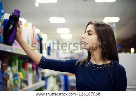 Woman choosing detergent in supermarket - stock photo