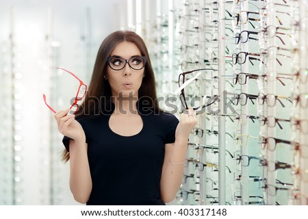 Woman Choosing Eyeglasses Frames in Optical Store - Cute girl deciding for glasses of different shapes and colors - stock photo