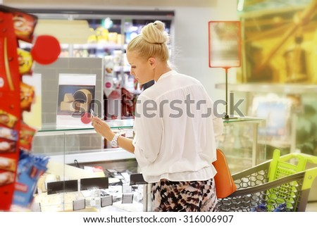 Woman choosing  food from a supermarket freezer. Checking list.