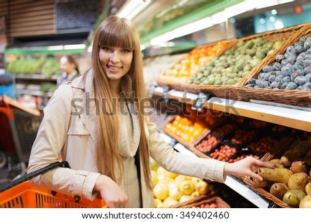 Woman choosing fruits at supermarket and holding pear - stock photo