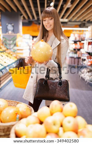 Woman choosing fruits at supermarket and holding pomelo - stock photo