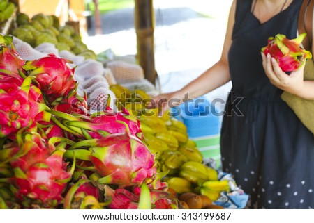 Woman choosing fruits in the open air fruit market in the village in Thailand