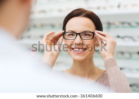 woman choosing glasses at optics store - stock photo